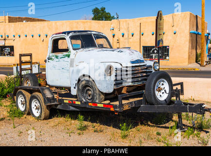 TAOS, NM, USA-8 JULY 18: The body of a crica-1950 Chevrolet pickup truck sets on a trailer on a corner in downtown Taos. - Stock Photo