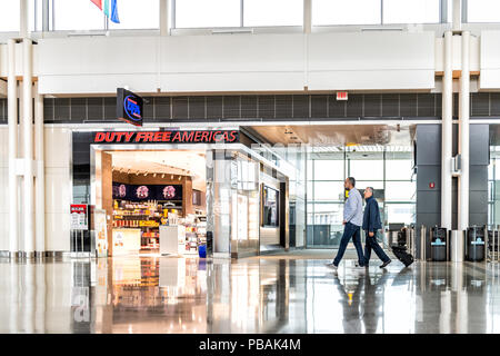 Dulles, USA - June 13, 2018: Duty free Americas shop, store with people, passengers walking with luggage, baggage, bags at Dulles International Airpor - Stock Photo