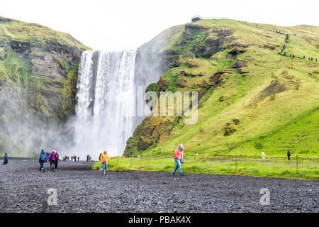 Skogafoss, Iceland - June 14, 2018: Waterfall, cliff, green grass hills, many tourists, people walking on gravel road, mist, water falling off cliff i - Stock Photo