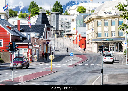 Akureyri, Iceland - June 17, 2018: Cityscape, skyline view of small town, city, street, road, people walking on sidewalk, houses, buildings, restauran - Stock Photo