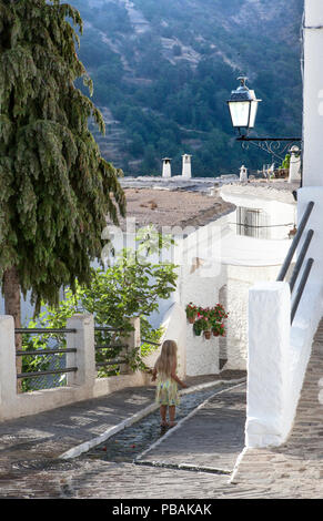 Little blonde girl having fun with water channel in the middle of the street at Alpujarras village. Rural tourism with children in Spain concept - Stock Photo
