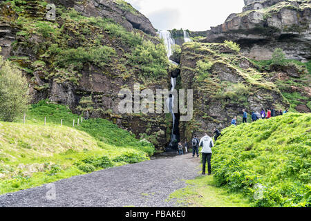 Gljufrabiu, Iceland - June 14, 2018: People walking by entrance to canyon with waterfall by cliffs, water flowing, dirt gravel road, green grass, foli - Stock Photo