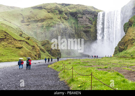 Skogafoss, Iceland - June 14, 2018: Waterfall, cliff, green grass hills, many tourists, people, couples walking with umbrella on gravel road, mist, wa - Stock Photo