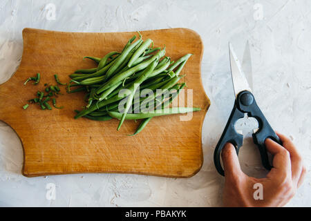 Green Beans on a grey concrete background wooden board cutting with scissors healthy food cooking - Stock Photo