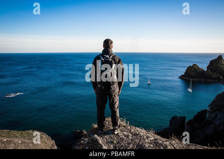A rear view of a male backpacker or hiker standing on a high cliff and admiring an awe inspiring sea view - Stock Photo