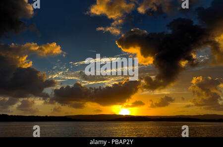 A spectacular inspirational brightly coloured Cumulonimbus cloudy sea water tropical panoramic sunrise seascape featuring silhouettes - Stock Photo