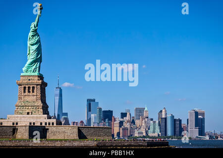 The Statue of Liberty with New York City in the background. - Stock Photo