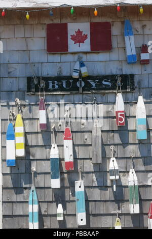 Close-up photo of brightly coloured buoys hanging on a wall beneath a sign saying 'BUOYS' and the Canadian maple leaf flag; North Rustico, PEI - Stock Photo