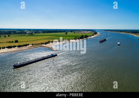 aerial view commercial ship crossing the River Rhine in an area of the Netherlands - Stock Photo