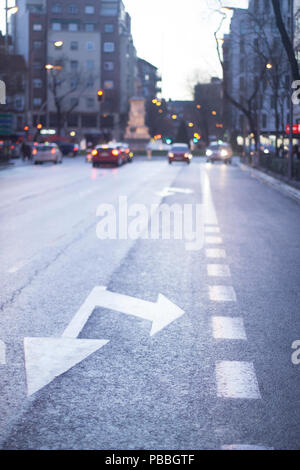 City street in Madrid Spain road traffic control markings arrows indicating lanes straight on and righ turn. - Stock Photo