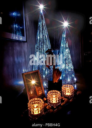 Three low candles and three stars at the top of the crystal cliffs in a decorative piece symbolizing a Christmas theme with trees, flares, and stars - Stock Photo