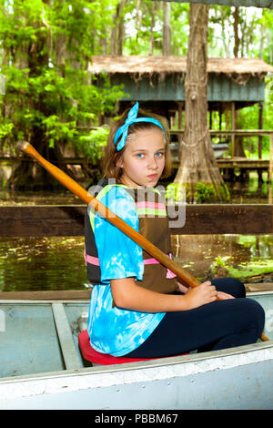 A pre-teen girl sits in a metal canoe, ready to launch, with paddle in hand and a smirk on her face.  She is in front of a swampy background with cypr - Stock Photo