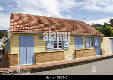 Cute yellow home on Allee des Arlesiens in Les Anses d'Arlet village, Grand Anse, Martinique (French West Indies), France - Stock Photo