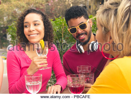 Multiracial group of students having a great time at cafe bar outdoor. Happy friends socializing in a party at restaurant outside. Summer, warm, frien - Stock Photo