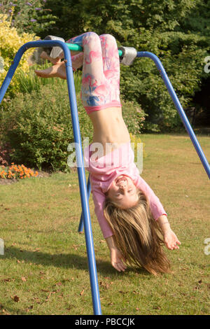six year old girl doing gymnastics acrobatics on apparatus in back garden for play, UK. - Stock Photo