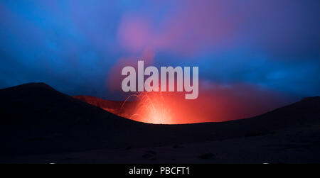 Volcanic Eruption with lava, from the crater edge at night - Mt Yasur, Tanna Island - Stock Photo