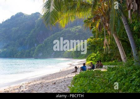Local boys sitting on the beach in Tikopia, Solomon Islands - Stock Photo