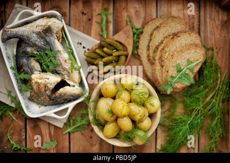 lunch. baked dorado and young potatoes. Marinated cucumbers and black bread. in rustic style, - Stock Photo