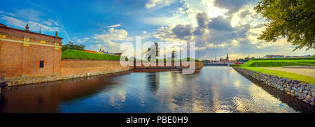 Panoramic landscape with fortress walls, water moat of Kronborg castle and town at sunset. Helsingor, Denmark - Stock Photo