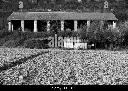 Railway engine shed and farmer's field store in the hamlet of Lexos, in the commune of Varen, Tarn et Garonne, Occitanie, France in in black-and-white - Stock Photo