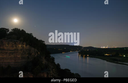 Texas, USA. 27th July 2018. The Blood Moon shines brightly with hues of red and orange next to the planet Mars over the skyline of Austin, Texas on the evening of Friday July 27th. Credit: Eva Hawker/Alamy Live News - Stock Photo