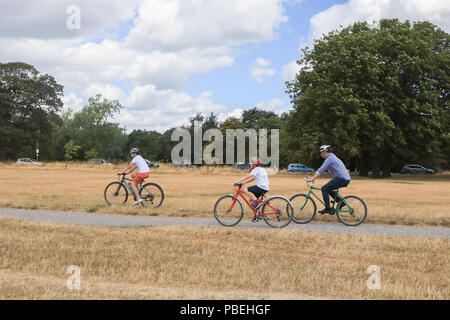 London UK. 28th July 2018. Cyclists ride  on  Wimbledon Common with cooler temperatures forecast for the weekend after the hottest July on Friday recorded Credit: amer ghazzal/Alamy Live News - Stock Photo