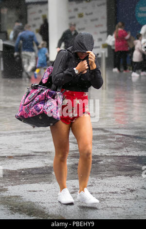 Woman in shorts during heavy shower in Blackpool, Lancashire, UK Weather. 28/07/2018. Heavy rain and strong winds at the coast with gales forecast for later in the day.  Credit: MediaWorldImages/AlamyLiveNews - Stock Photo