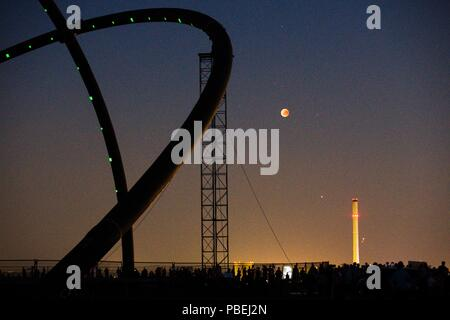 Recklinghausen, Germany. 27th July, 2018. Stargazers can follow the lunar eclipse on the Hoheward slagheap between Recklinghausen and Herne. On the one side the sun sets and on the other the moon rises. Credit: Jana Bauch/dpa/Alamy Live News - Stock Photo