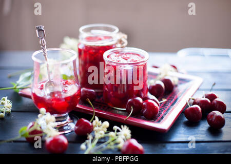 jam from cherry, in cans. winter desserts. dark photo. spring white flowers - Stock Photo