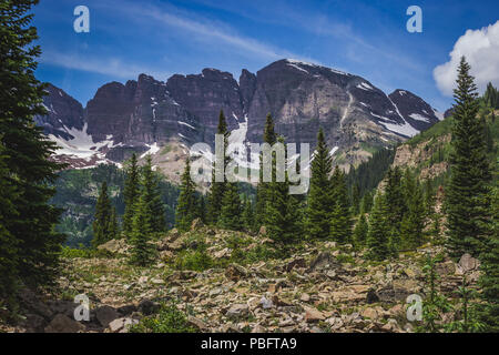 Majestic Maroon Bells peaks seen from the rugged Crater Lake Trail on a sunny day with blue sky in summer near Aspen, Colorado - Stock Photo
