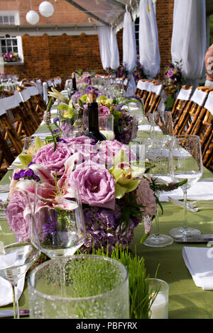 A long table that is beautifully decorated at a reception in the mountains of North Carolina - Stock Photo