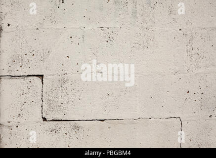 Texture of an old wall, big bricks painted in white with one crack on one side. - Stock Photo