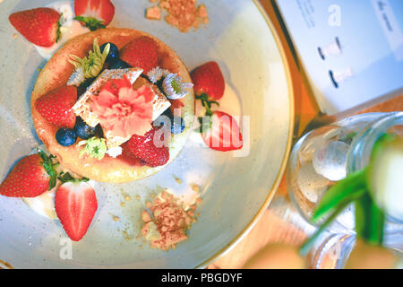 Top view Hot pan cake topped with fresh strawberries , blueberries, honeycomb and fresh flower for decoration on white dish - Stock Photo