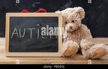 Autism and school. Teddy bear and a blackboard. Autism text drawing on the blackboard - Stock Photo