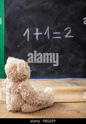 School class math. Teddy bear looking at a simple equation on a blackboard.  One plus one equals two - Stock Photo