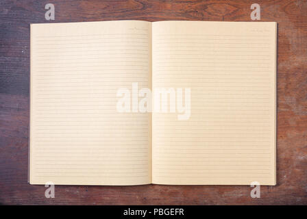 Open blank school notebook or diary, old fashioned, isolated on wooden desk, space for text, top view - Stock Photo