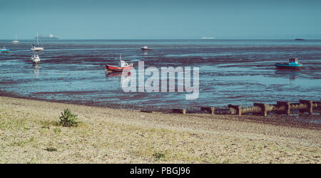 small boats photographed during low tide in Shoeburyness, Essex, UK - Stock Photo