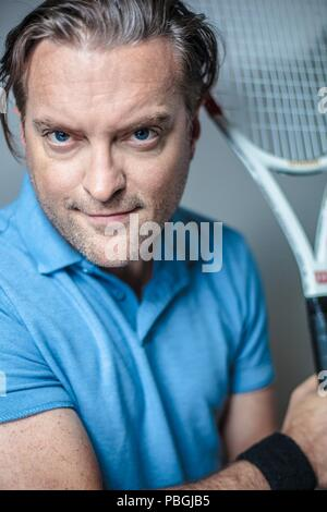 portrait of a handsome man with a tennis racket - Stock Photo