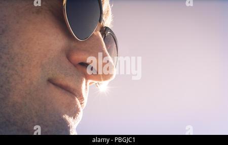 closeup photo of a man facing the sun in sunglasses - Stock Photo