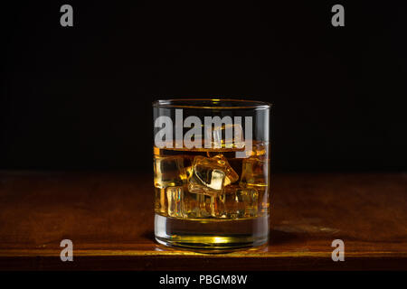 Bourbon whiskey on whiskey glass with rustic and dark theme - Stock Photo