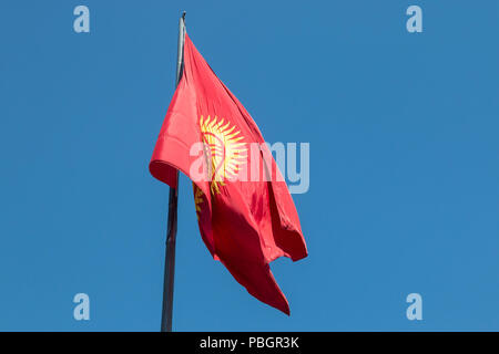 Flag of Kyrgyzstan, featuring a red background and a yellow sun, flying over Ala Too Square in central Bishkek, the country's capital city. - Stock Photo