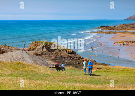 6 July 2018: Bude, Cornwall, UK - Tourists on Compass Hill looking down over busy Summerleaze Beach during the summer heatwave, as people cool off in  - Stock Photo