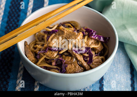 Steak, noodles and purple cabbage closeup in bowl with chopsticks - Noodle meal - Stock Photo