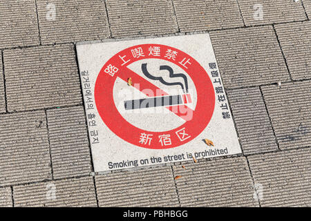'Smoking on the street is prohibited' sign on sidewalk; Tokyo, Japan - Stock Photo