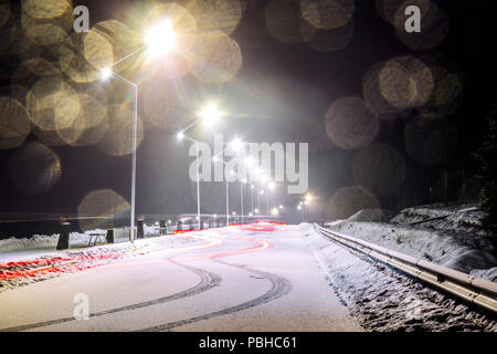 long exposure image a passing car on a snowy road - Stock Photo