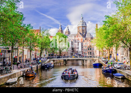 Tour boat at famous dutch canal on a sunny day, surrounded by traditional old buildings, in Red Light District, Amsterda, Netherlands. - Stock Photo