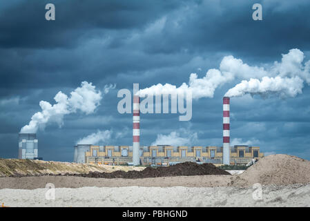Coal ower plant smokestacks emitting smoke by chimneys - Stock Photo