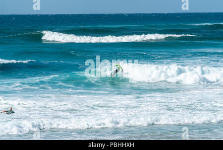 COOLANGATTA, AUSTRALIA - JULY10 2018; Wide surf beach with surfer riding through white wave foam with deep turquoise sea behind - Stock Photo