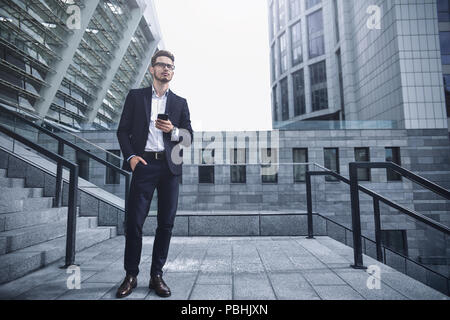 Handsome successful businessman in elegant suit outdoors walking on street in the city. - Stock Photo