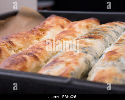 Pie with cheese and spinach in baking tray - Stock Photo